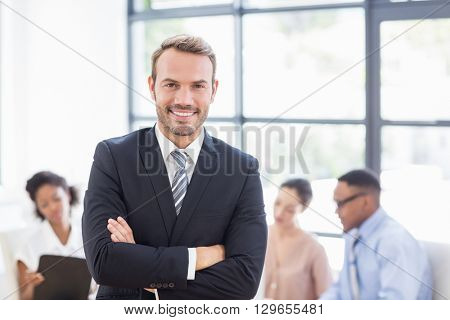 Happy businessman standing with arms crossed in office while colleagues discussing in background