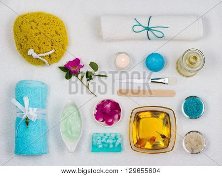 View from above. Set For Spa. On White Towel. Dec Towel Sponge Salt Soap Candle Cream.
