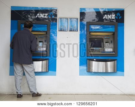 Hanoi, Vietnam - May 14, 2016: Asian man making a transaction on an automatic teller machine (ATM) of ANZ commercial bank in Hanoi capital. ANZ is one of Australia's four largest banks.
