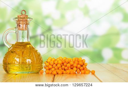 Bunch of sea buckthorn and oil bottle closeup on a green background