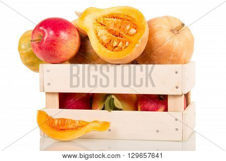 Small pumpkins in a wooden box isolated on white background close-up