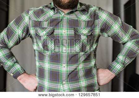 stout bearded man in a checked shirt standing arms akimbo resolutely