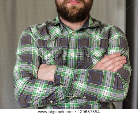 stern bearded man in a plaid shirt standing arms crossed