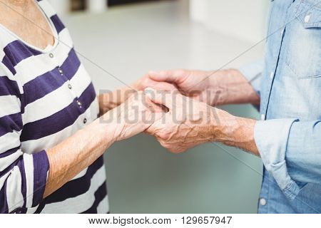 Midsection of senior couple holding hands at home