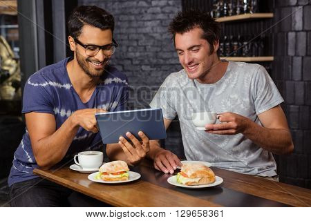 Friends using a tablet in a coffee shop