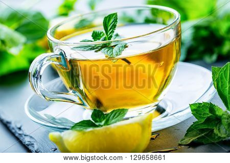 Tea. Mint Tea. Herbal tea. Mint leaf. Mint leaves. Tea in a glass cup mint leaves dried tea sliced lime. herbs tea and mint leaves on a slate plate in a restaurant or teahouse tea room