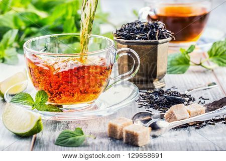 Tea. Mint Tea. Herbal tea. Mint leaf. Mint leaves. Tea in a glass cup mint leaves dried tea sliced lime. herbs tea and mint leaves on a slate plate in a restaurant or teahouse tea room.