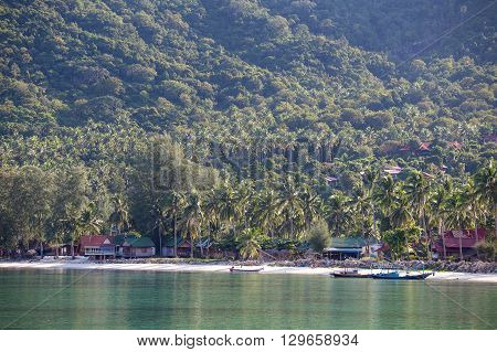 KOH PHANGAN THAILAND - NOVEMBER 16 2015 : Chaloklum beautiful beach with palm trees and small bungalows for tourists. On the island Koh Phangan each month passes full moon party for tourists