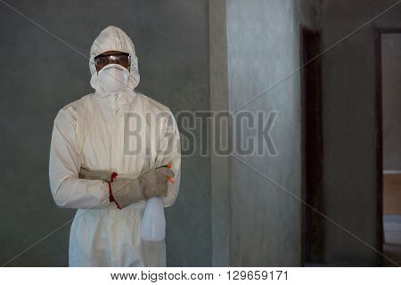 Pest control man standing with spray bottle in home