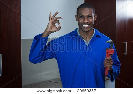 Plumber with a wrench showing ok hand sign at home