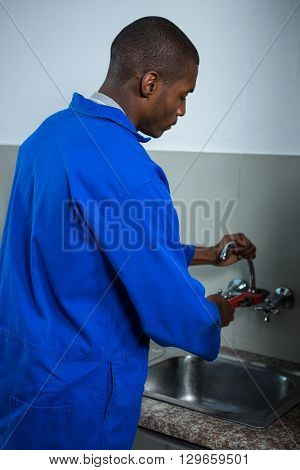 Plumber fixing the sink with wrench in the kitchen