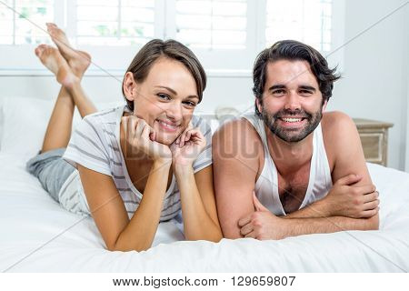 Portrait of happy couple lying on bed at home