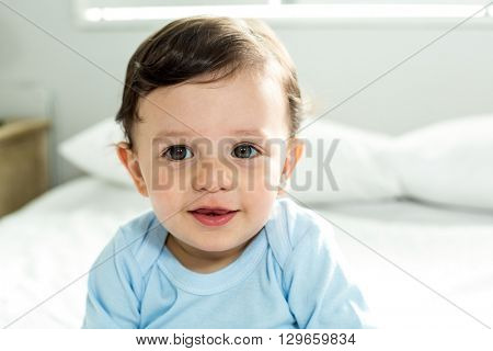 Close-up portrait of cute baby boy sitting on bed at home