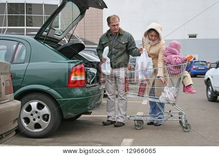 family put shop bags in car
