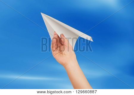 Businesswoman throwing white paper plane on a background of blue sky