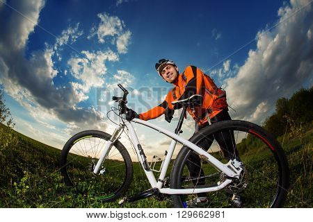 Man Cyclist in Orange Jersey with bike on sunset
