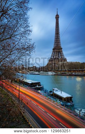 Eiffel Tower at twilight on cloudy winter morning with the Seine River and car light trails. Paris, Grenelle, 7th Arrondissement, France