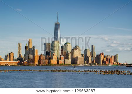 New York City Manhattan Financial District skyscrapers at sunset with Hudson River and old wooden pilings. Lower Manhattan skyline