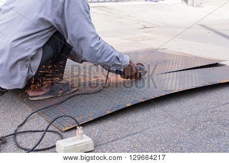 Worker cutting a metal by electric cut tools manufacturing