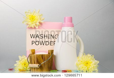 Washing powder, laundry softener, clothes pegs and flowers on a gray background