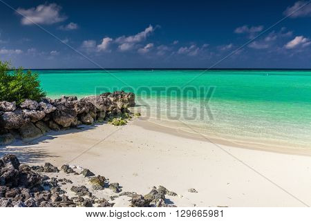 Small secluded beach protected by rocks on a tropical island with soft sand