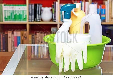 Household cleansers are standing on the glass table in the living room. Horizontally. Plastic bottles spray rubber gloves all in the green plastic tub. All potential trademarks are removed.