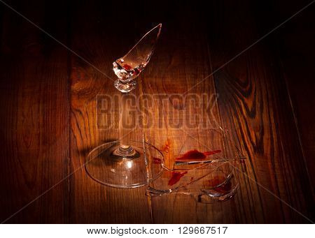 Broken glass fragments and blood on a wooden background