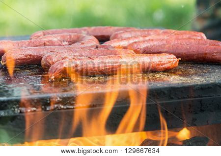 Roasting sausages on the hot stone in nature