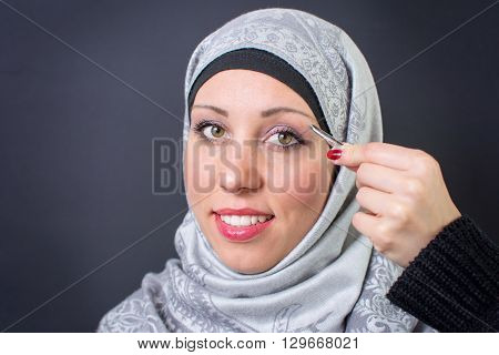 Beautiful muslim woman using her eyebrow tweezers