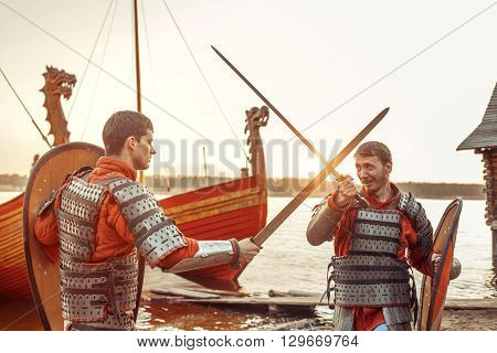 Battle Of Two North Warriors With Swords And Shields. Warships On The Background.