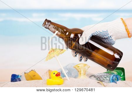 Hand removes bottle and trash on the beach