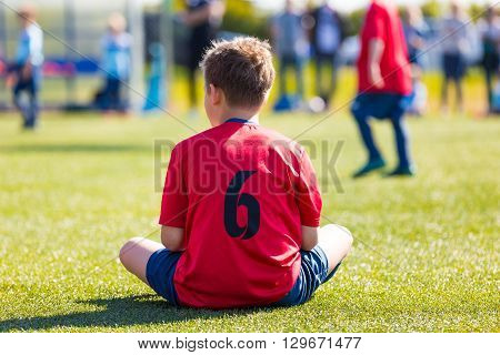 Child dressed in sports clothes sitting on green grass of sports stadium. Boys is waiting on his turn to play soccer footbal match.