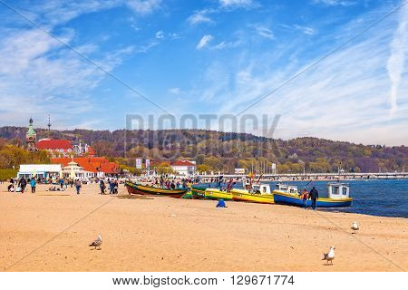 SOPOT, POLAND - MAY 03, 2016: Baltic coast beach scene of many people walking along the coast on a sunny day. Sopot is a famous tourist resort located in Poland.