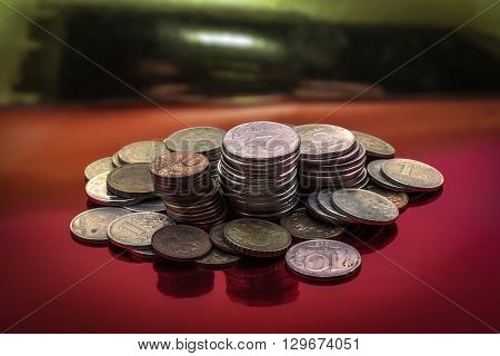 Coins of small denomination stacks on red background blurred