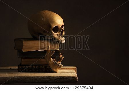 Human Skull with Jawbone on old Book