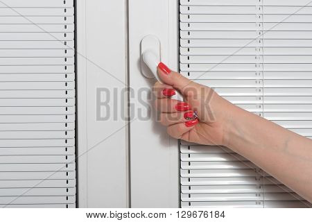Female hand whith manicure and blinds at window
