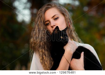 Nice, pretty, lovely, cute, careful, beautiful, attractive blondie, blonde girl, girl with light, wavy, long, curly hair with cat, black cat. Girl with cat. Girl hug cat. Girl love cats. Cat Lady. Love to animals, cat