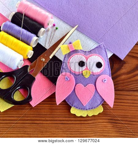 Felt owl toy, felt sheets, scissors, thread, pins, needle on a brown wooden background