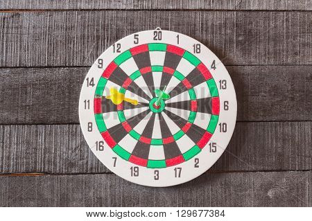 dart board with darts arrow in the target center on wood background.