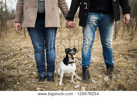 Pregnant Couple Standing Together Holding Hands In Spring Forest