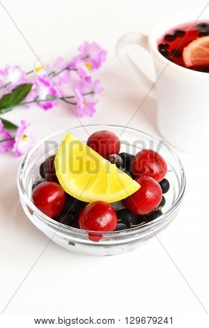 Frozen cherries and black currants, a slice of fresh lemon, Cup of compote