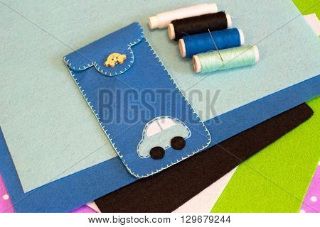 Felt case for mobile phone. Felt sheets, set of colorful threads