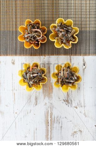 Tartlets filled with seaweed salad on bamboo placemat against rustic wooden background top view with copy space