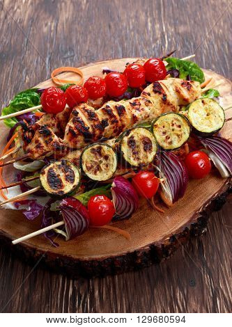 Roast Chicken filet kebab with cherry grilled on BBQ. tomatoes, zucchini and red onions on bamboo sticks
