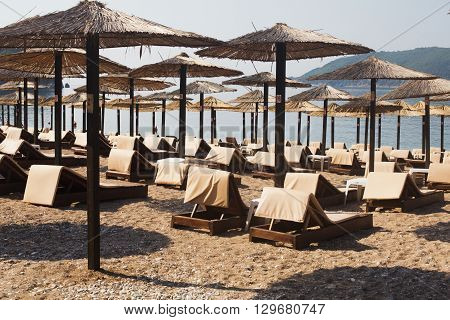 Rows of brown wooden lounge chairs and straw beach umbrellas on sea beach in the morning. Budva, Montenegro