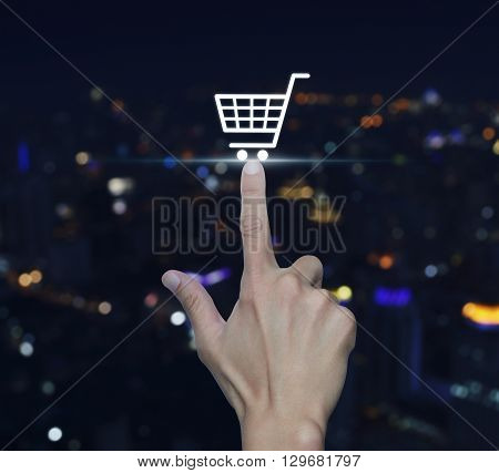 Hand pressing shopping cart icon over blurred light city tower background Shopping online concept