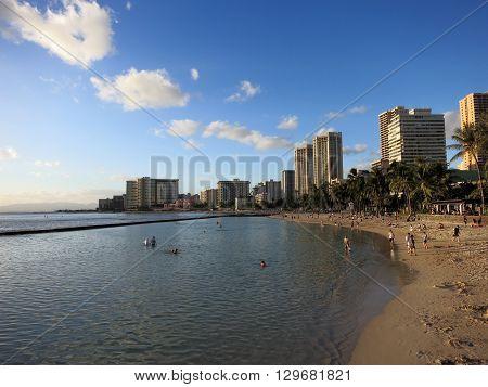 WAIKIKI - FEBRUARY 7: People play in water and beach in Waikiki at dusk on February 7 2016.
