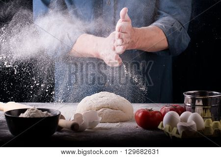 Baker prepares the dough on table, male hands knead the dough with flour, homemade dough for bread or pizza, top view, rustic style