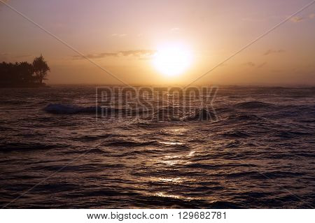 Sunset over the ocean with waves moving to shore on the North Shore of Oahu.