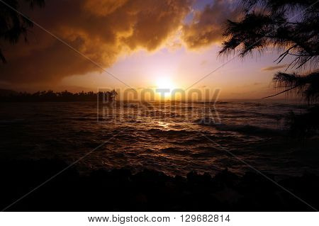 Sunset over the ocean with waves moving to shore on the North Shore of Oahu with clouds in sky.